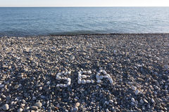 The sign Sea made from white pebbles. On pebble beach on the sea Stock Image