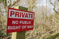 Newly erected Private sign seen on the border of public land in a forest. The sign, seen together with some barbed wire is used to warn public footpath users stock photos