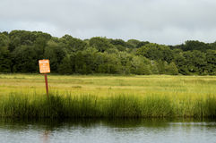 Sign in shellfish bed. Or breeding area. Tall grasses and a field with forest in background Royalty Free Stock Images
