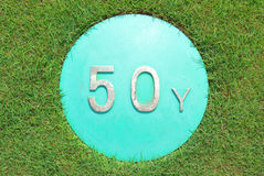 The sign show 50 yard distance on green golf course. Stock Photos