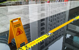 Sign showing warning of caution wet floor and mind the step. In front of the building Stock Images