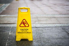 Sign showing warning of caution wet floor outdoors.  Royalty Free Stock Photography