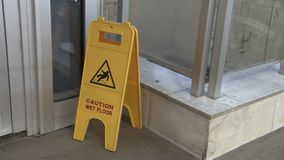 Sign showing warning icon of wet floor. Yellow signboard standing on concrete surface. Exhibition hall caution notice.  stock video footage