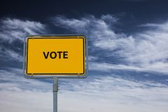 Sign showing the word VOTE, in the background is a stormy blue sky royalty free stock image