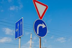 A sign that shows the road and turn only right to the background of a brilliant blue sky.  stock photos