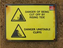 Sign at Sidmouth sea front telling of the dangers of rising tides and falling cliffs royalty free stock image