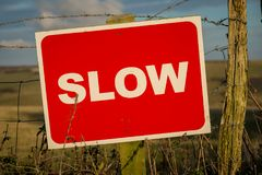 Sign: Slow, with a fence and a blurry background. Seen near Seaford Head in East Sussex, UK royalty free stock photo