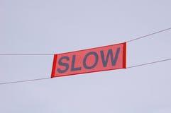 Sign Slow in sky. On ski slope stock image