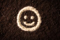 Sign of a smiling face drawn on a brown background royalty free stock photography