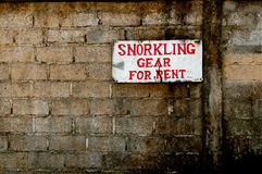 Sign for snorkelling gear for rent on old brick wall. An old sign indicating snorkeling gear for rent placed on an old brick wall Stock Image