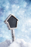 Sign In The Snow. Blank sign in the snow with festive winter background royalty free stock photo