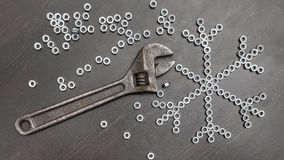 Sign snowflake made up of screws nuts on a dark wooden table Stock Photo