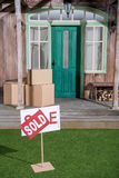 Sign sold on green grass and cardboard boxes stacking on porch Royalty Free Stock Photography