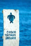 Sign with Spanish warning to the care of nests of sea turtles on Stock Photography