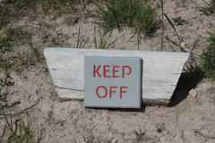Sign stating KEEP OFF Royalty Free Stock Photo