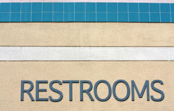 Sign stating RESTROOMS. A sign on a colorful stuccoed wall that states RESTROOMS Royalty Free Stock Photography