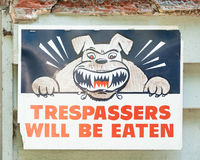 Sign stating TRESPASSERS WILL BE EATEN with Angry Dog Symbol. No trespassing sign on wall stating TRESPASSERS WILL BE EATEN with symbol of angry guard dog stock image