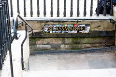Sign on steps leading down to Grassmarket in Edinburgh, Scotland. Grassmarket sign covered in stickers in Edinburgh, Scotland during the Fringe Festival 2018 stock photography
