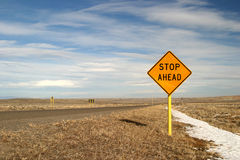 Sign Stop Ahead. A yellow traffic sign that reads Stop Ahead. A little snow on the ground and a lonely highway. Could be great for travel, warnings, cautionary royalty free stock photography