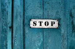 Sign ''stop'' on the grunge wooden door. Close up of a sign saying ''stop''on the grunge wooden background Royalty Free Stock Image