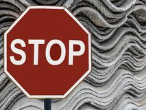 Sign stop and a stack of sheets of asbestos. royalty free stock images