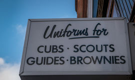 Sign From a Store Selling Unifroms for Boy Scouts and Girl Guide. Sign Outside A Shop Selling Uniforms For Childrens Clubs in Glasgow Scotland, United Kingdom Royalty Free Stock Photo