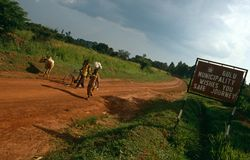 A sign beside a stretch of dirt road, Gulu, Uganda. Stock Image