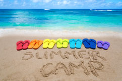 Sign. Summer camp and color flip flops on sandy beach by the ocean in sunny day Stock Images