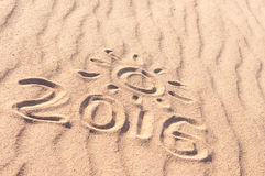 Sign 2016 and sun written on sandy beach. Summer travel concept Royalty Free Stock Photos