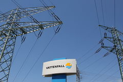 Sign of the Swedish power company Vattenfall and  transmission tower in the background Royalty Free Stock Photos