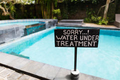 A sign beside swimming pool. SaidSorry,water under treatment Royalty Free Stock Photography