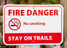 Sign and Symbol FIRE DANGER No Smoking STAY ON TRAILS. Red and white sign on fence stating FIRE DANGER No Smoking STAY ON TRAILS with symbol of cigarette in royalty free stock photos
