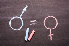 Sign, a symbol of a man and a woman. The concept of equality. A sign, a symbol of a man and a woman, is drawn in chalk. The concept of equality, equal rights stock photo