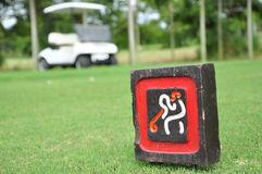 Sign at tee off with golf cart on golf course Royalty Free Stock Photo