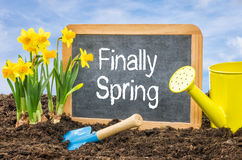 Sign with the text Finally Spring. Sign in the flower bed with the text Finally Spring Royalty Free Stock Image