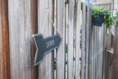 Sign with the text `love` hangs in a garden Royalty Free Stock Image