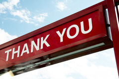 Sign - THANK YOU. Dark red background and white letter, blue sky stock photography