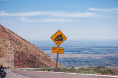 Sign of traffic alerts downhill slope. Sign of traffic alerts downhill slope 10 %, reduce speed and use a lower gear. Drive with caution stock photography