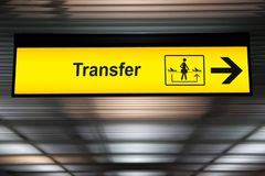 Sign transfer with arrow for direction for transit passenger. To change air plane for destination. yellow transfer for connecting flight sign at the airport royalty free stock image