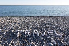 The sign Travel made from white pebbles on pebble beach on the s. Ea Stock Image