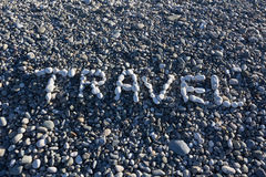 The sign Travel made from white pebbles on pebble beach on the s. Ea Stock Photos