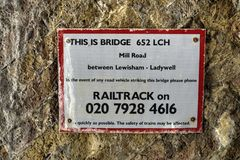 Sign on Underside of Railway Bridge Providing Contact Details in Case of Vehicle Strike. London, United Kingdom - May 13, 2019: Sign on underside of railway stock photography