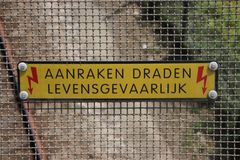 Sign at a viaduct in dutch `aanraken dragen levensgevaarlijk` which means touching wires is dangerous above railroad track. Sign at a viaduct in dutch `aanraken stock images