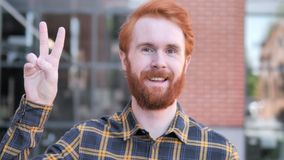 Sign of Victory by Redhead Beard Young Man Standing Outdoor. 4k high quality, 4k high quality stock video
