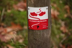 Sign for walking direction and behaviour rules of a clog path on the Veluwe in Gelderland, The Netherlands. Sign for walking direction and behaviour rules of a royalty free stock image