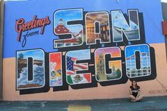 """Greetings from San Diego, California, USA. The sign on the wall is saying """"Greetings from San Diego"""". A girl is sitting in front of the wall royalty free stock images"""