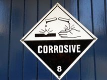 A sign warning care to be taken because the area has corrosive chemicals present. In an industrial work area stock images