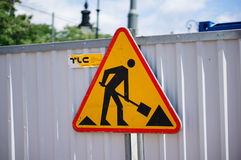 Sign warning for construction. Work in progress triangle shaped sign on a barrier of the TLC construction company in Poznan, Poland Stock Photography