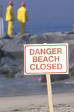 A sign warning, danger�beach closed with cleanup crews in the background Stock Photography