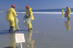 A sign warning, danger�beach closed with cleanup crews in the background Royalty Free Stock Photography